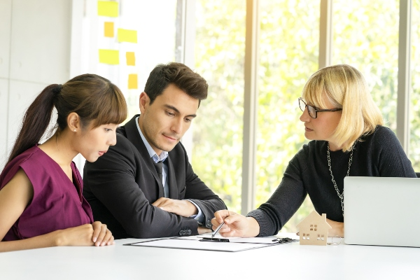 A recruitment specialist helps two job seekers understand a document.